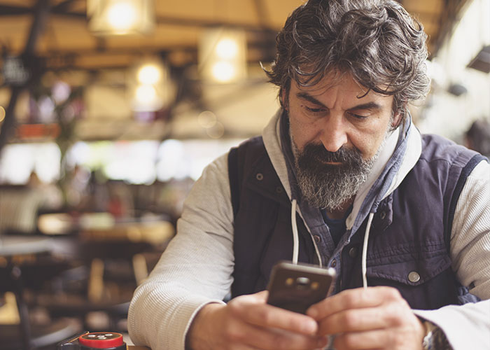 Man in a coffee shop monitoring from his phone